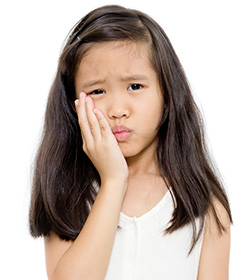 young girl holding cheek in pain
